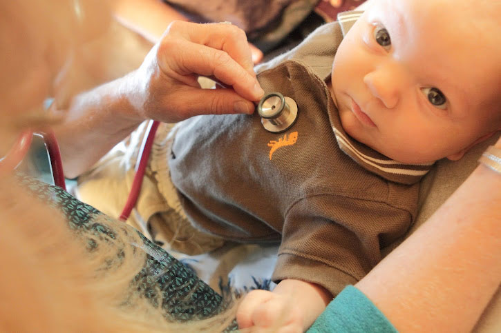 Dr Zieman examining baby with stethoscope